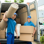 42611693 - two male workers carrying carpet and cardboard boxes in front of van
