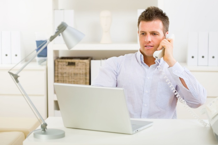 business man working on laptop computer at home and calling on phone.