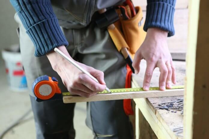 Tradesman measuring wood