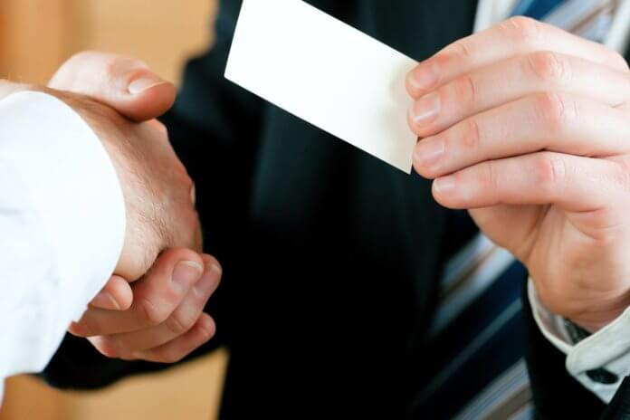 Men shaking hands and exchanging business cards