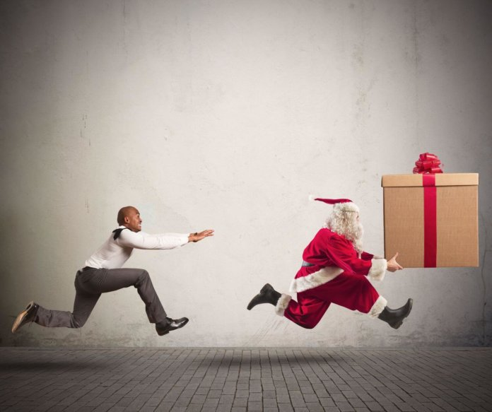 Angry man chasing santa claus holding a large gift