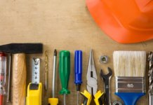 Neatly laid out construction and tradesman tools on wood background.