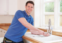 Photo of a happy plumber, smiling at camera whilst working on a sink.