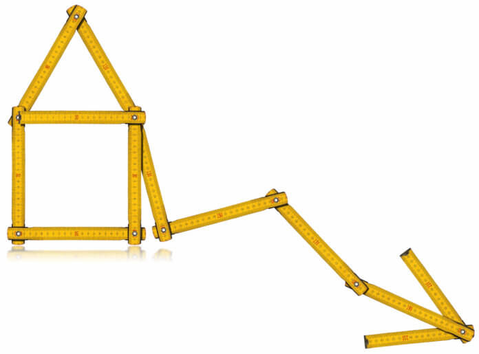 Measuring tape in the shape of a house with an arrow poiting down to indicate a decrease in growth.