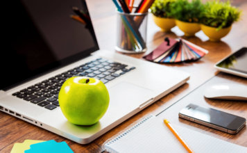 Photograph of a 'healthy looking', neat and tidy desk in an office. With a green apple, plant and immaculate laid out stationary.