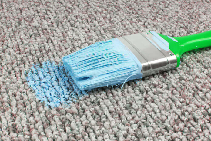 A green decorators paintbrush covered in blue paint has been dropped onto a carpet, staining it.